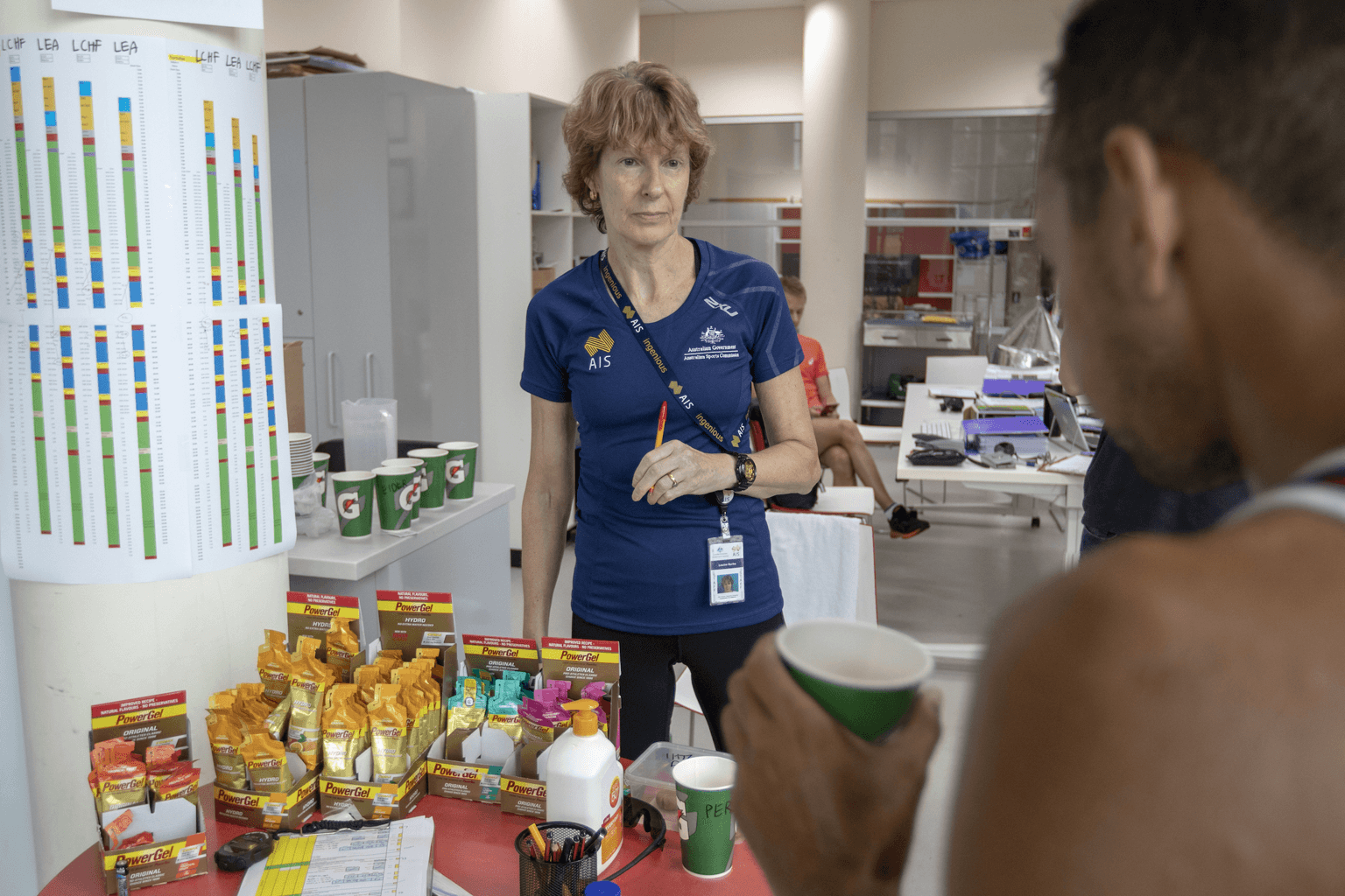 Professor Louise Burke stands behind a table with sport supplements and papers, while and athlete drinks from a cup.