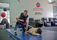 Athlete and coach stretch on the AIS recovery mat 2012